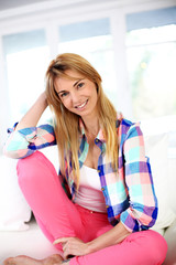 Cheerful blond woman relaxing at home in sofa