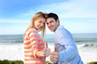 Couple showing thumbs up in front of the sea