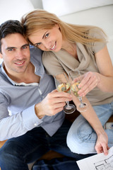 Cheerful couple celebrating with glass of sparkling wine