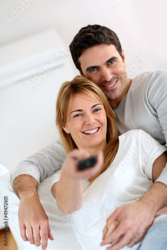 Sweet couple in sofa watching tv