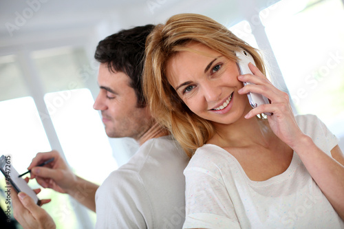 Couple using smartphone, sitting back to back