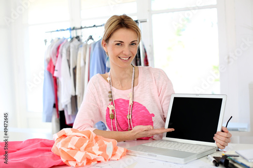Smiling fashion designer showing laptop screen