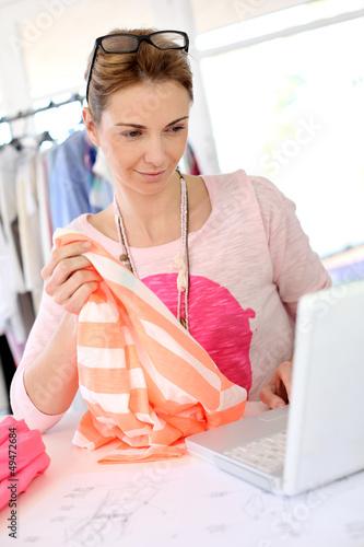 Woman designer in workshop looking at laptop