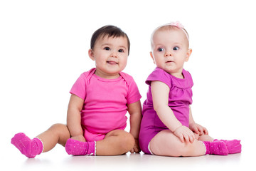 Funny babies girls sitting beside on floor