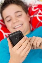 Junge liegt entspannt mit Handy / Smartphone im Bett