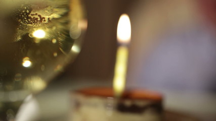 Glass of champagne and candle in the tiramisu cake.