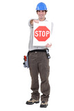 portrait of craftsman holding stop sign