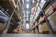 Rows of shelves with cardboard boxes on modern warehouse in stor