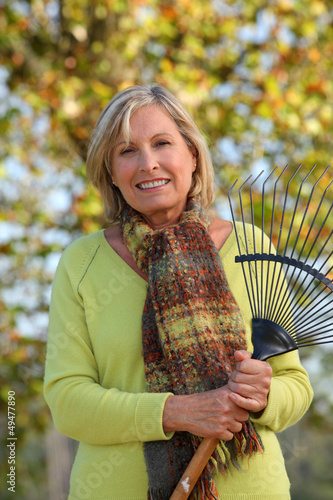 Woman raking leaves in a yard