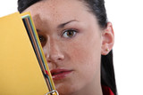 Shy woman hiding behind folder