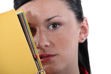 Shy woman hiding behind folder