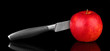 Red apple and knife on isolated on black