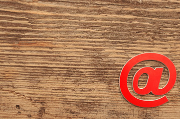 red e-mail symbol on wooden background with copy space