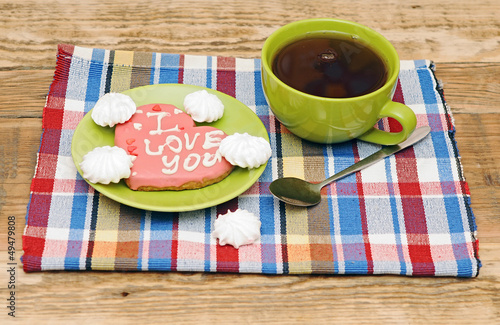 tea cup with sweet heart shaped cookie on colorful napkin