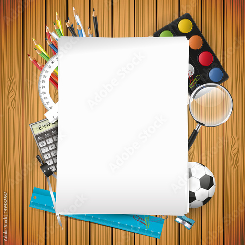 School supplies and empty paper on wooden background