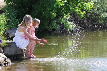 mother and her little daughter squirting water at the lake
