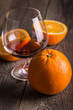 Orange with glass of whiskey or brandy on wooden table.