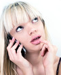 Attractive blond girl pondering while phoning