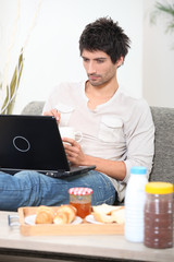 young having breakfast with computer on a sofa