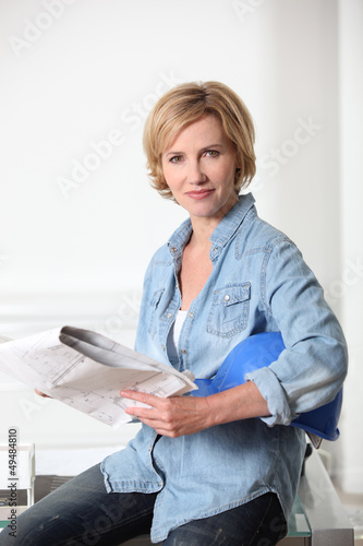 Blond woman holding helmet and blueprints