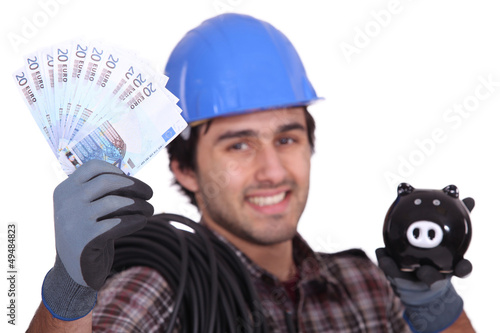 Construction worker with bills and piggy bank in hands