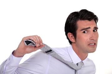 businessman in panic pulling his tie