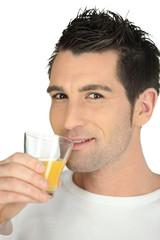 Man drinking glass of orange juice