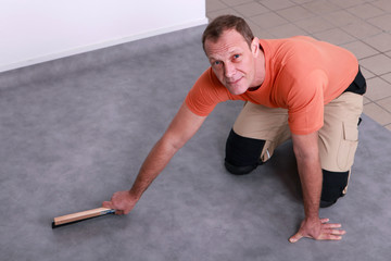 Man fitting a linoleum floor