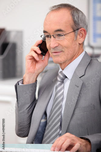 65 years old man wearing a grey suit and calling