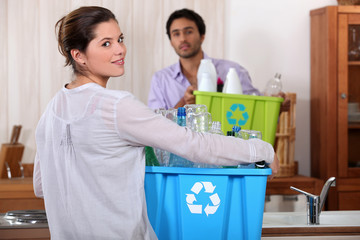 Man and woman preparing to recycle plastic bottles