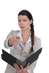 A businesswoman pointing at the camera.