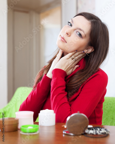 young woman uses cosmetic cream