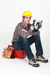 Carpenter sat on tool box with electric circular saw