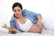 Pregnant woman stroking her pregnant belly while reading
