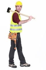 Worker carrying sledge-hammer over shoulder