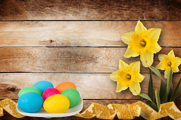 Pastel background with multicolored eggs and narcissus to celebr
