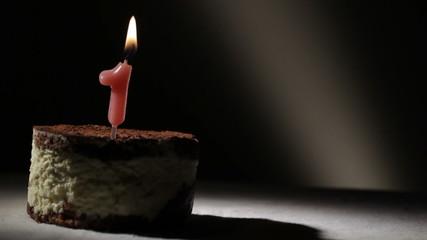 Candle one in tiramisu cake.