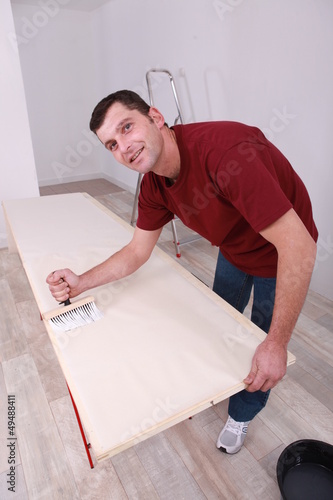 Man painting wooden plank