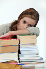Young woman laying her head on a stack of books