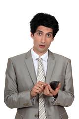 Wide-eyed businessman sending a text message