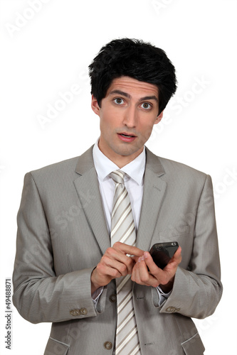 Wide-eyed businessman sending a text message