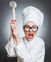 Angry woman cook trying to hit with a hammer