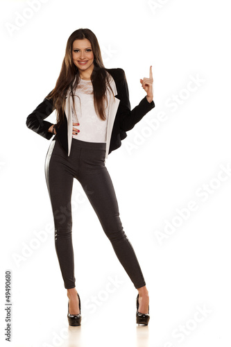 pretty brunette smiling and pointing a finger in the blank