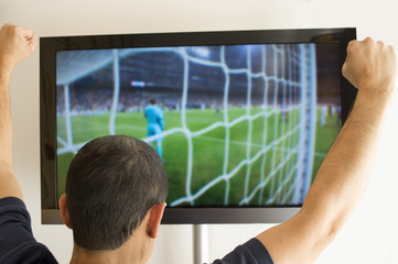 man watching a football game on tv with arms up