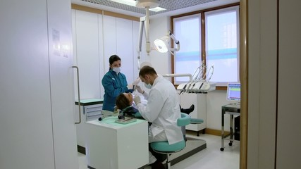 Dentist and assistant checking dental hygiene of client