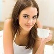 Young woman drinking coffee, at home