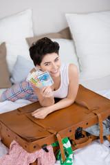 lächelnde frau mit koffer zeigt geldscheine