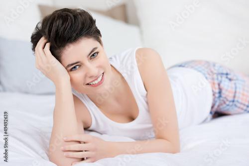 lächelnde frau liegt entspannt auf dem bett