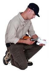 Plumber using pliers to fasten two parts together