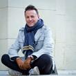 Homme 40s assis sur un mur en centre ville